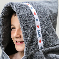 Child wearing a grey hooded towel with personalised Stars trim - Sam