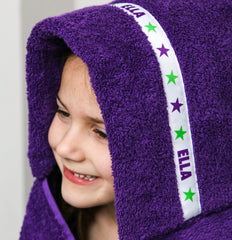 Child wearing a purple hooded towel with personalised Stars trim - Ella