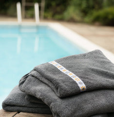 Jumbo grey hooded towel folded by the side of a swimming pool