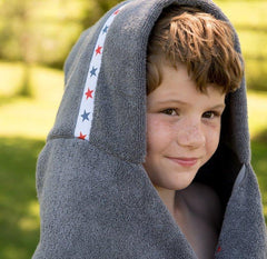 Boy wearing jumbo grey hooded towel with Red Stars trim
