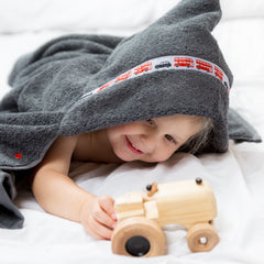 Child wearing a grey hooded towel with London Buses trim playing with a wooden toy