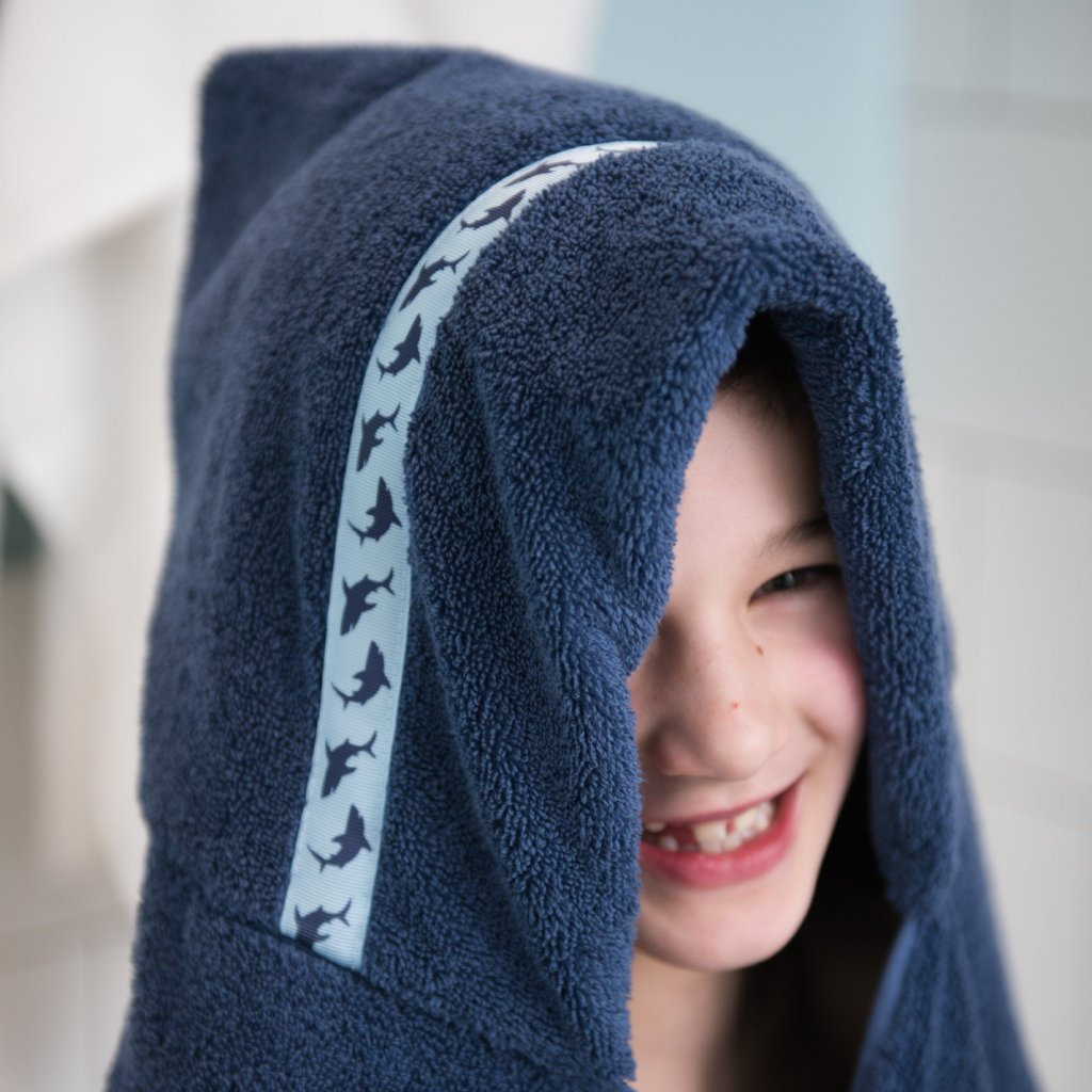Boy laughing whilst wearing jumbo navy blue hooded towel with Shark Attack trim
