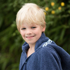 Boy wearing jumbo navy hooded towel with Shark Attack trim - hood down