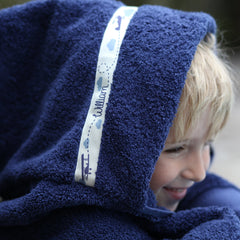 Child wearing personalised navy hooded towel with Areoplanes trim