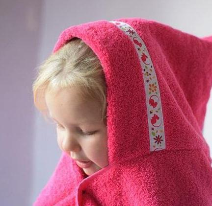 Girl wearing pink hooded towel with Two Bad Mice trim