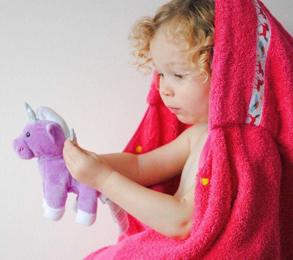 Child wearing pink hooded towel with Unicorns trim whilst holding a unicorn soft toy