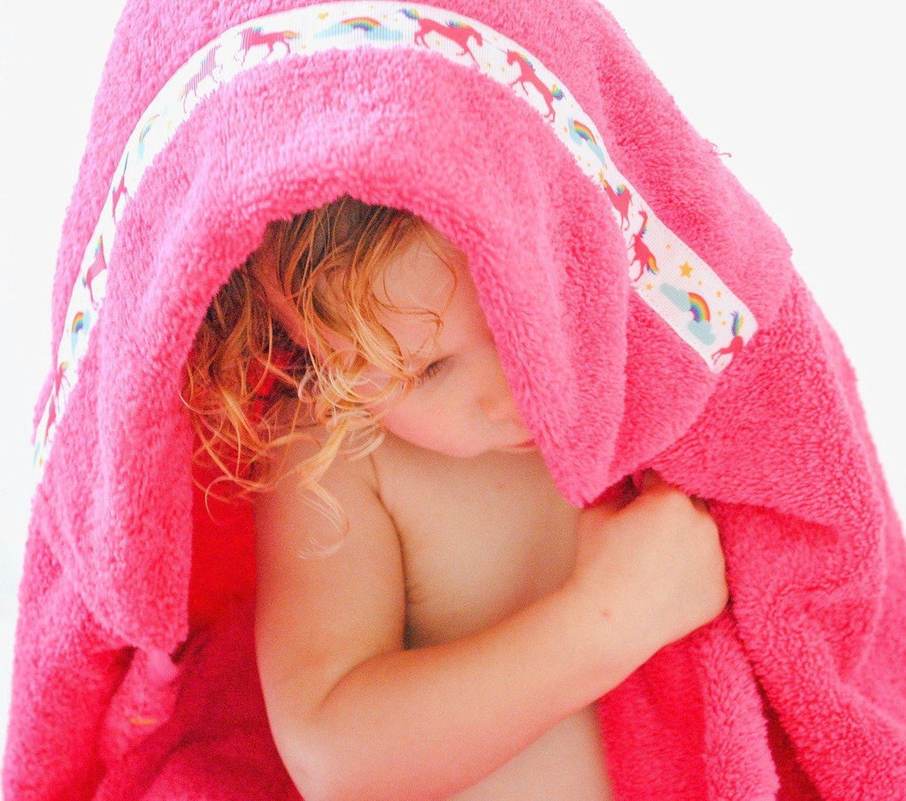 Child hiding under the hood of her standard pink hooded towel with Unicorns trim