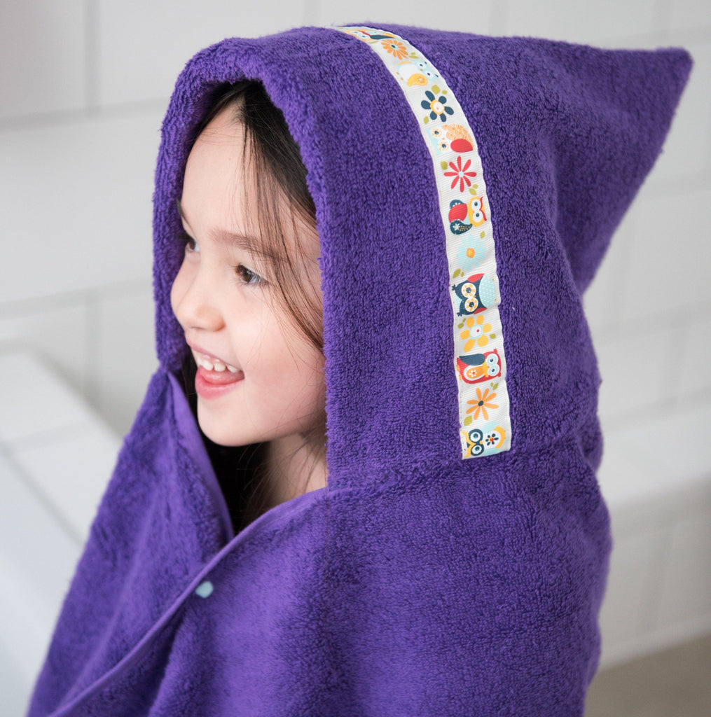 Child wrapped in purple hooded towel with Funky Owls trim