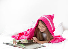 Child laying on her front reading a book wearing a jumbo pink hooded towel with Dragonflies trim