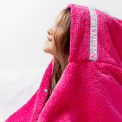 Side profile of a girl wearing a jumbo pink hooded towel with Dragonflies trim