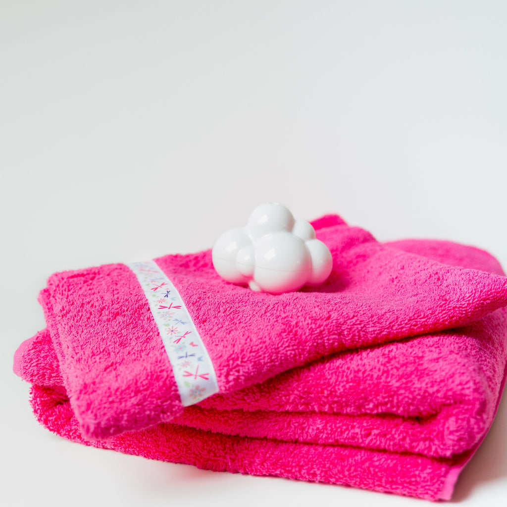 Pink jumbo hooded towel with dragonflies trim folded in a stack