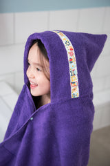 Child wearing jumbo purple hooded towel with Owls trim