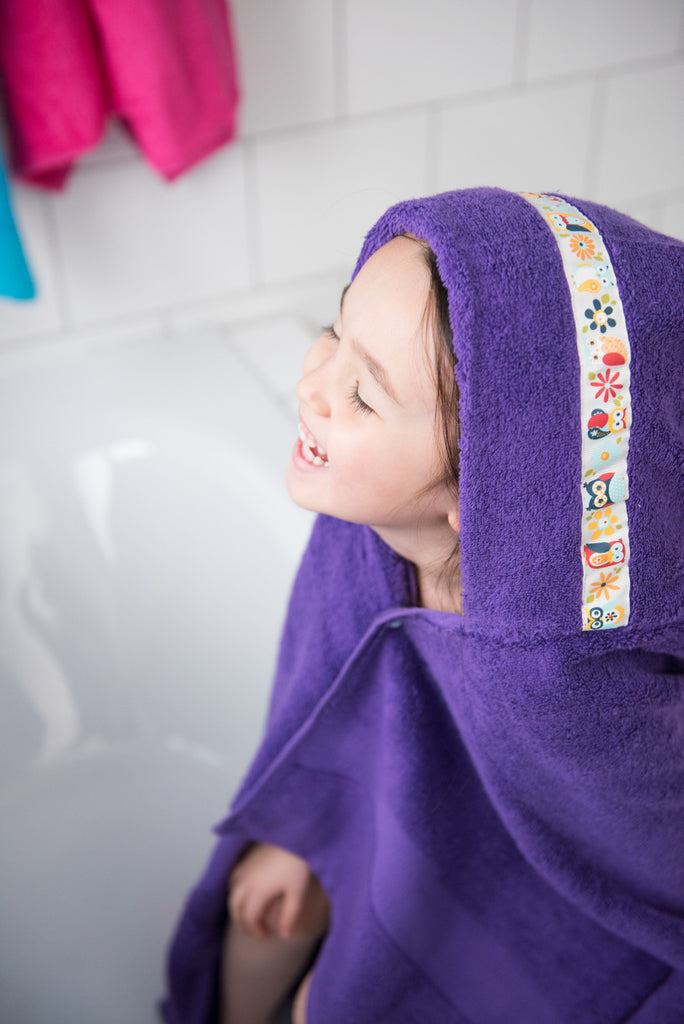 Child laughing wearing jumbo purple hooded towel with Owls trim