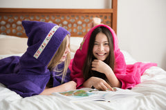 Two girls laying on a bed laughing whilst wearing hooded towels. One purple with Owls trim, the other pink