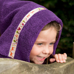 Girl peeking over a fence wearing a purple hooded towel with Orchard Creatures trim