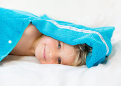Child laying on his side looking out from under the hood of his turquoise hooded towel with Polar Fishing trim
