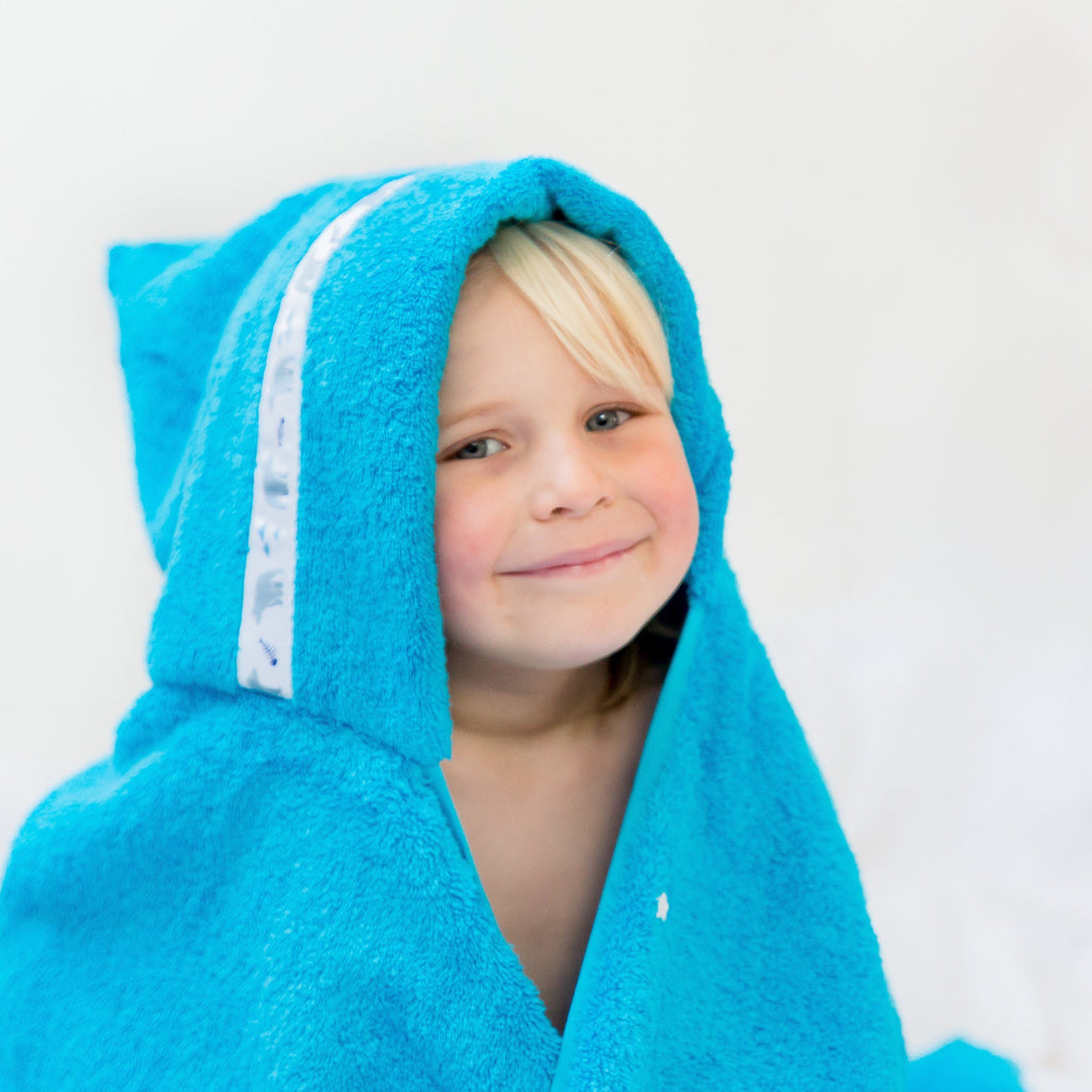 Happy child wearing turquoise hooded towel with Polar Fishing trim