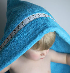 Child wearing turquoise hooded towel with penguins trim