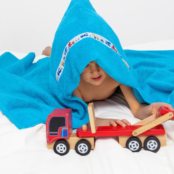 Child laying on his tummy wearing a turquoise hooded towel with Diggers & Dumpers trim and playing with a wooden toy