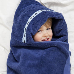 Child laying on bed with navy blue hooded towel with Dinosaurs trim