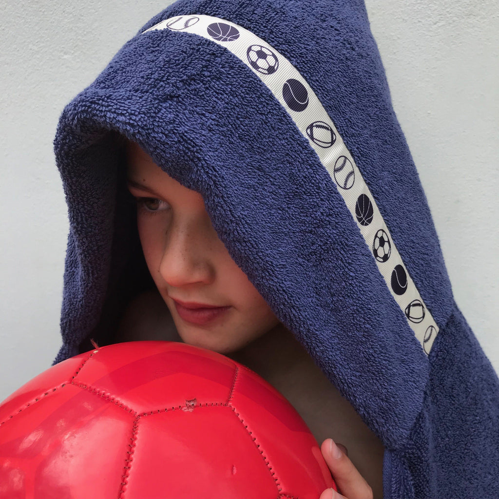 By holding a red football whilst wearing a blue hooded towel with Game Set Match trim