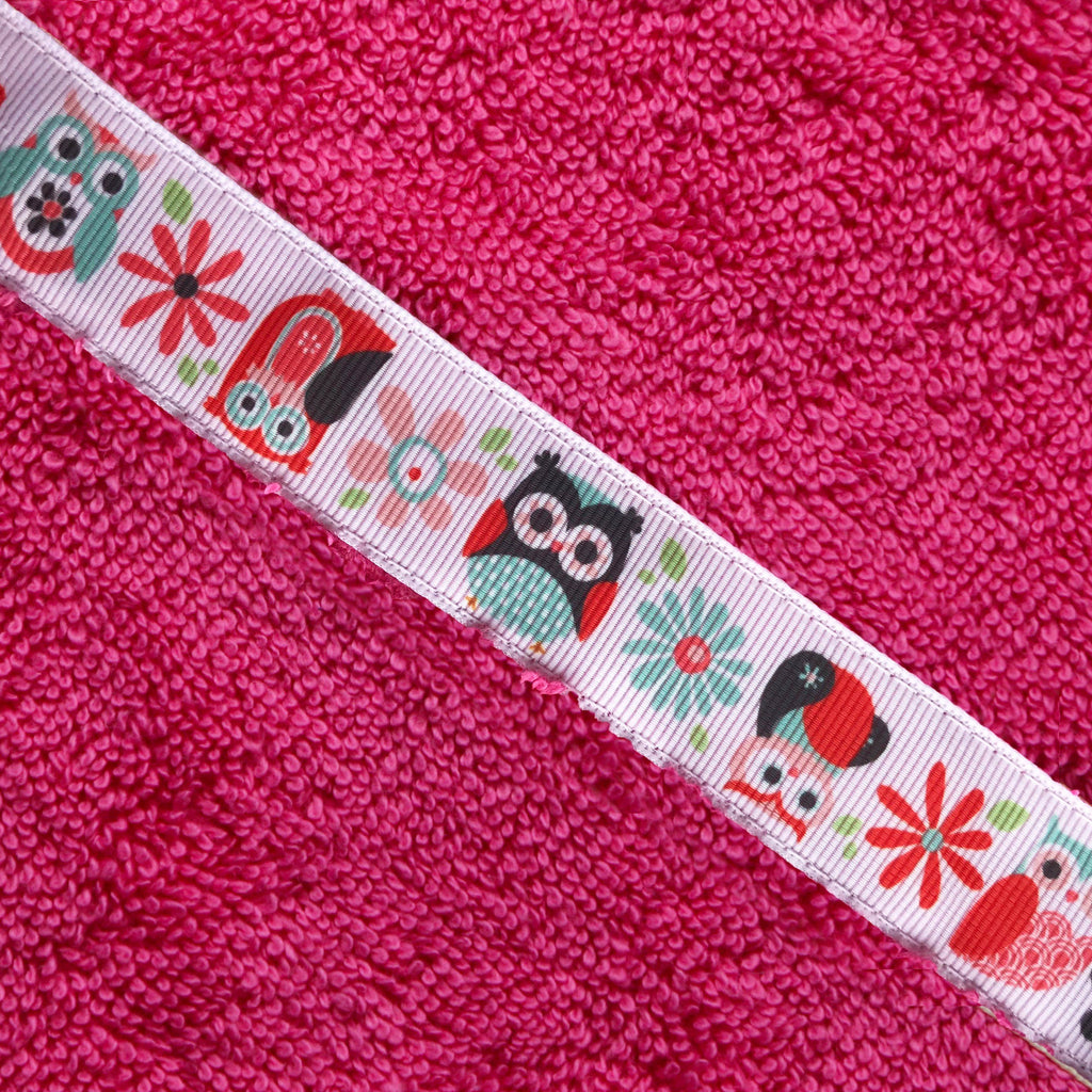 Close up on Owl ribbon trim on a pink towel