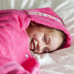 Girl laying on bed smiling snuggled in a pink hooded towel with owl trim