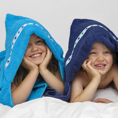 Two children laying on their fronts smiling whilst wearing hooded towels, one in a turquoise hooded towel with Blue Stars trim,  one in a navy hooded towel with Green Stars trim
