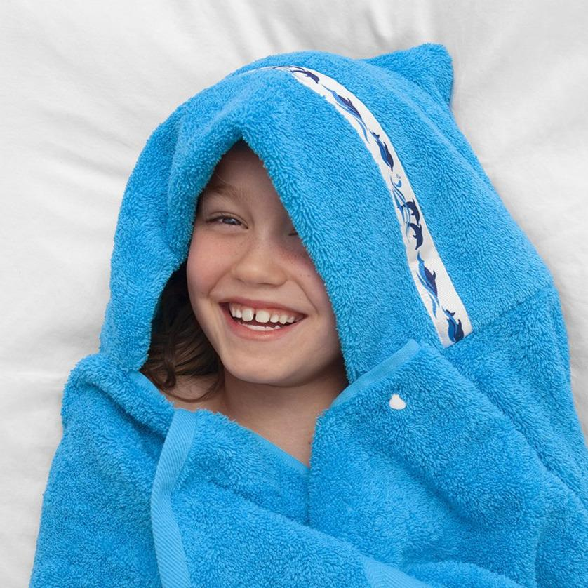 Child smiling and laughing whilst wearing a turquoise hooded towel with Dolphin Splash hooded towel