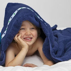Boy laid on his tummy with a hooded towel draped over him