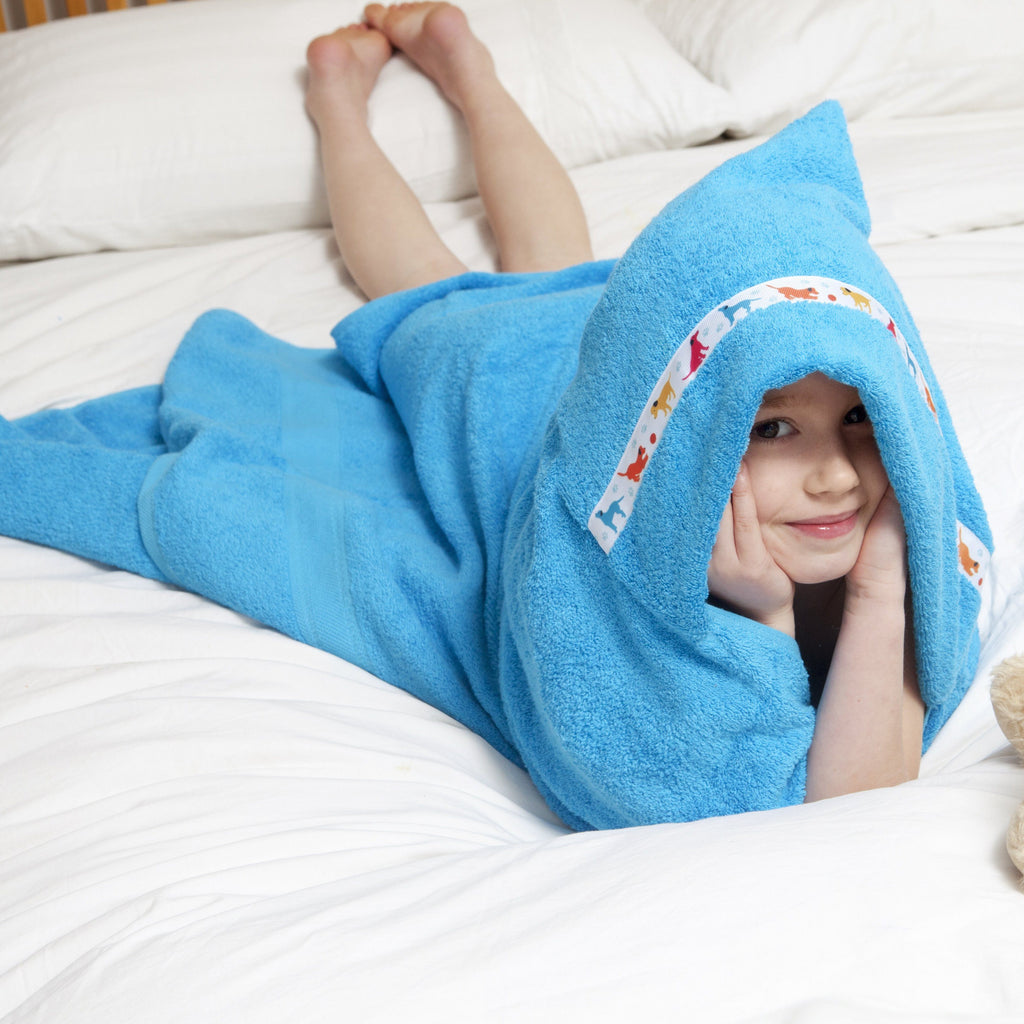 Child laying on her front wrapped up wearing a turquoise hooded towel with Puppy Love hooded towel