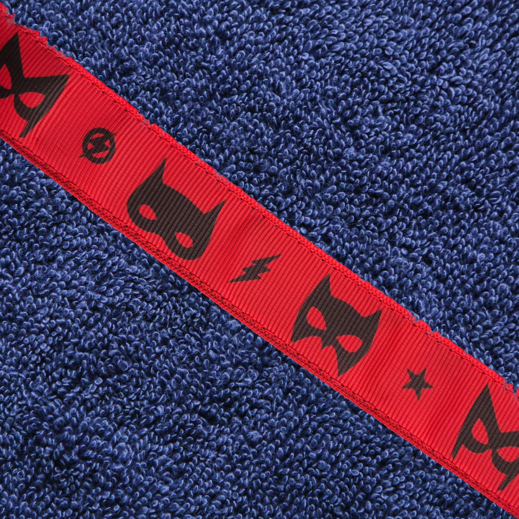 Close up of a red Superheroes trim on a navy blue hooded towel