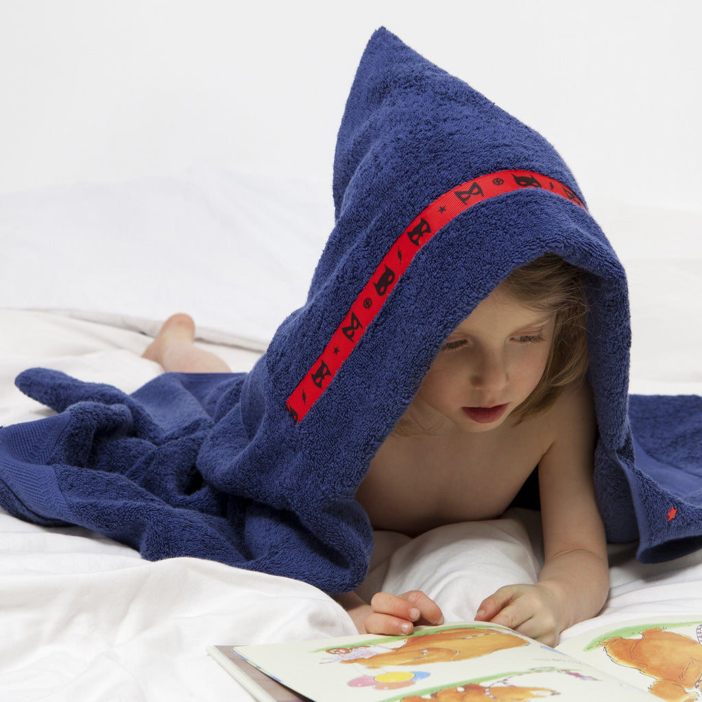 Child laying on his front reading a book whislt wearing a navy blue hooded towel with red superheroes trim around the hood