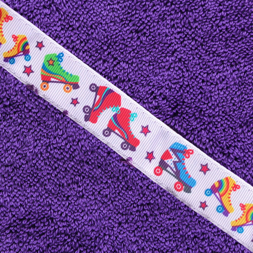 Close up of the Rollerskates trim of a purple hooded towel