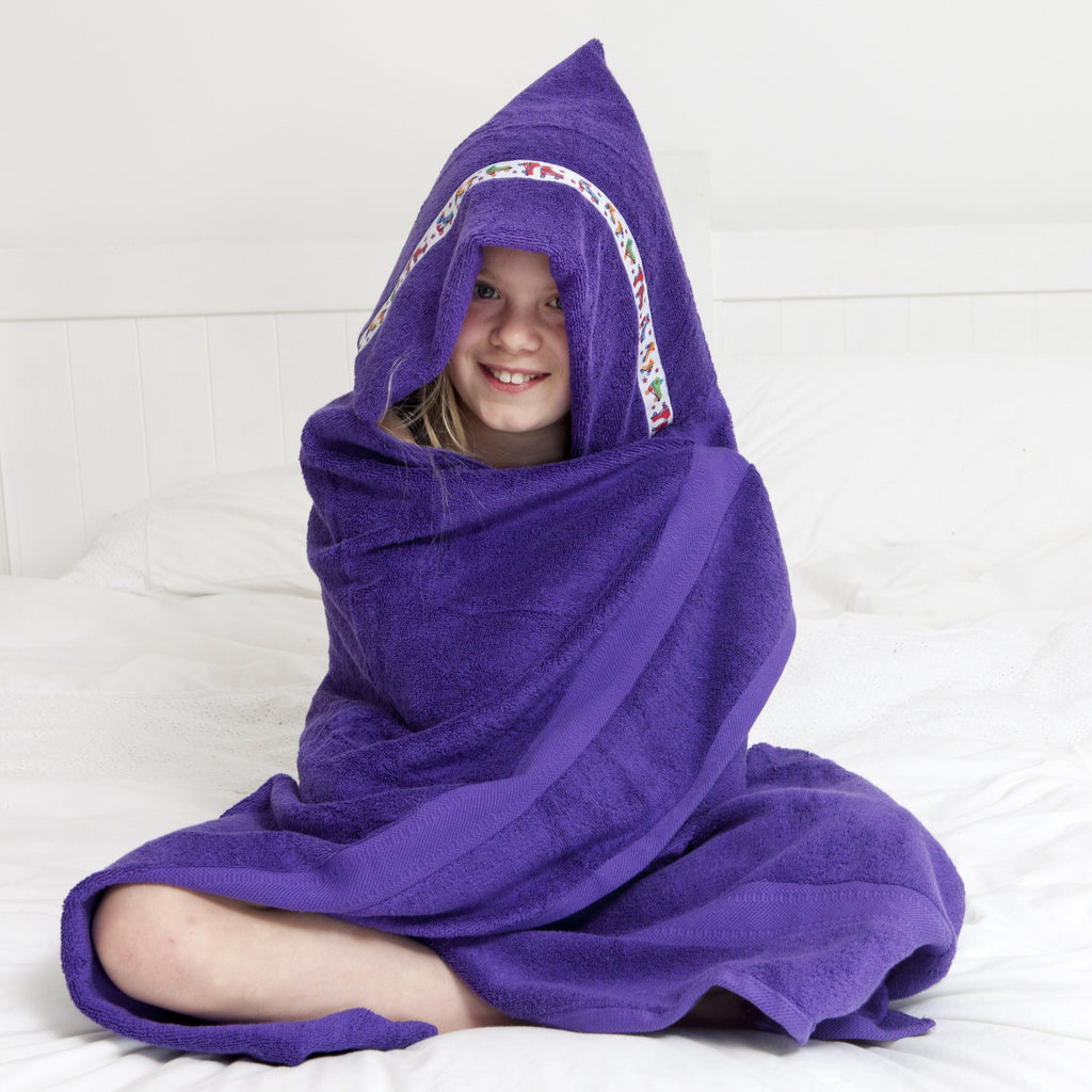 Girl sat cross-legged wrapped in a purple hooded towel with Rollerskates trim