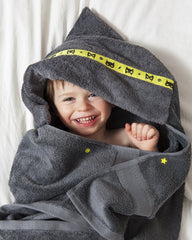 Child laid on a bed giggling wrapped up in a grey hooded towel with yellow superhero trim