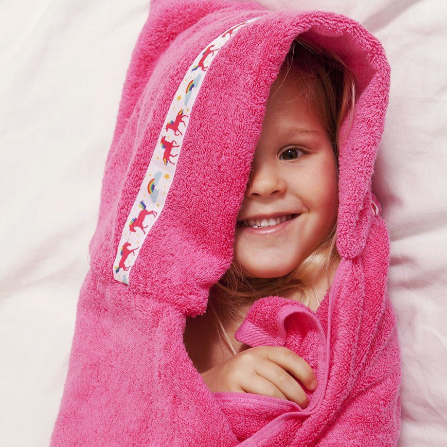 Child snuggled in pink hooded towel with unicorn trim
