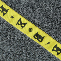 Close up of the Yellow Superheroes trim of a children's grey hooded towel