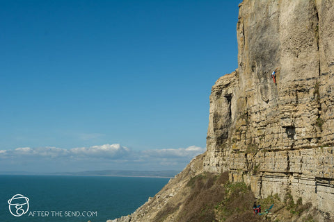 Pongoose Blog - Blacknor Central climbing area, Portland. Climber on cliff with blue sea behind.