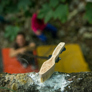 The Pongoose Climber 700 shown as a brushing stick brushing a chalky bouldering hold.