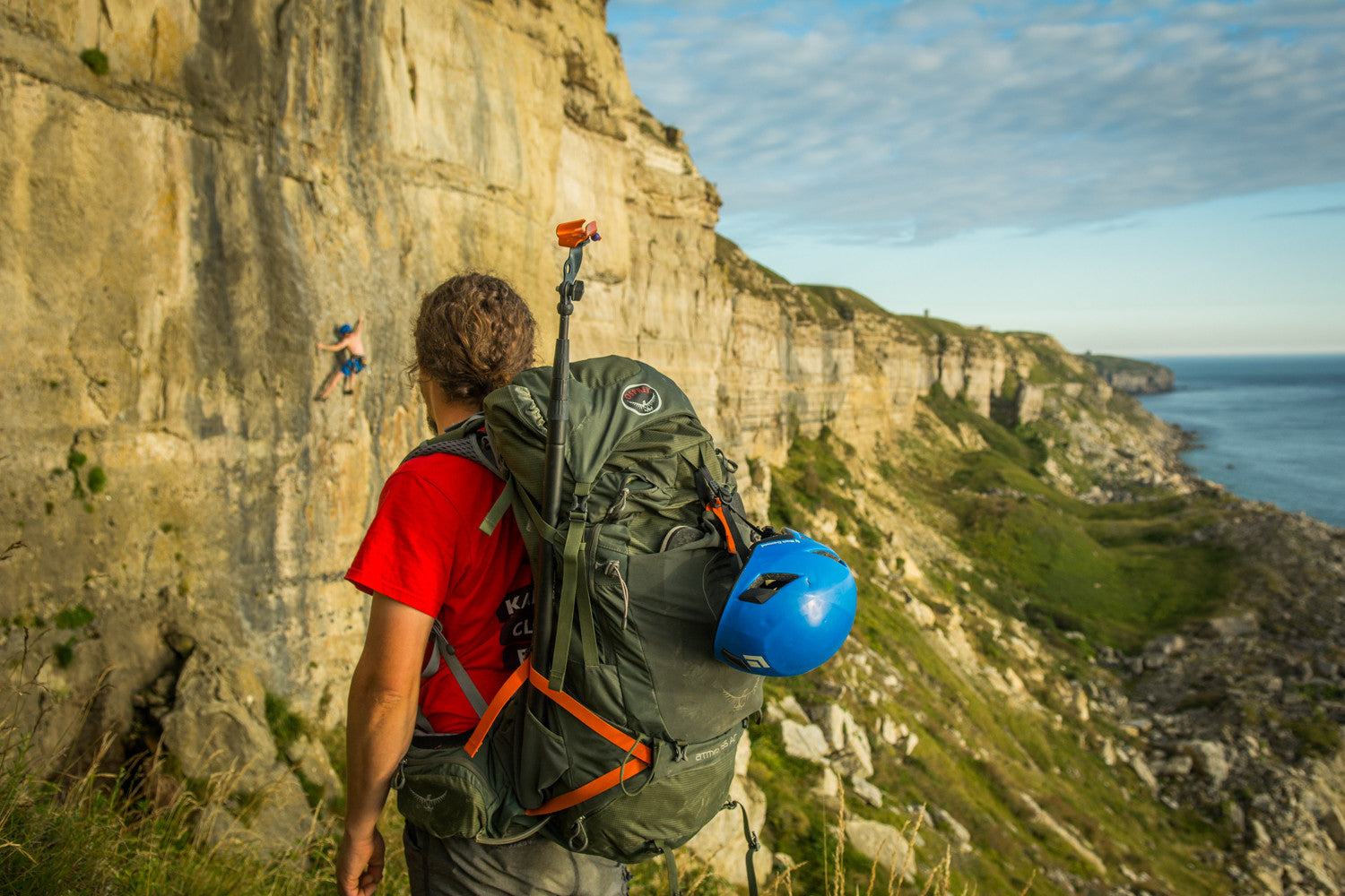 Pongoose Climber 700 featured attached to Osprey back pack at climbing area Blacknor, Portland, UK, with cliffs and blue sea in background.