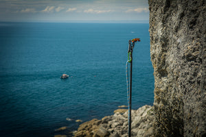 The Pongoose Climber 700 clipstick function; pole extended next to rock face with stunning blue sea and boat behind.