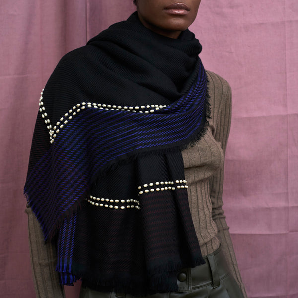 JANE CARR The Pearls Square in Midnight, black and blue checked lambswool scarf with pearl detail – model