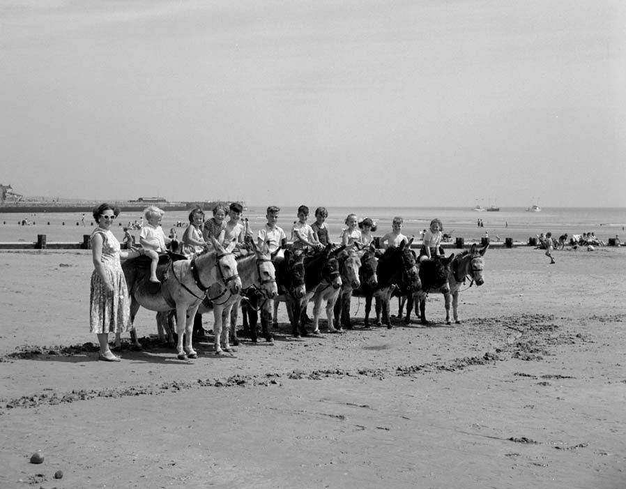 Children enjoy a donkey ride on the beach during the summer holidays