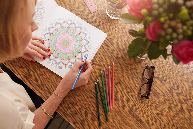 Woman sits at a table colouring in
