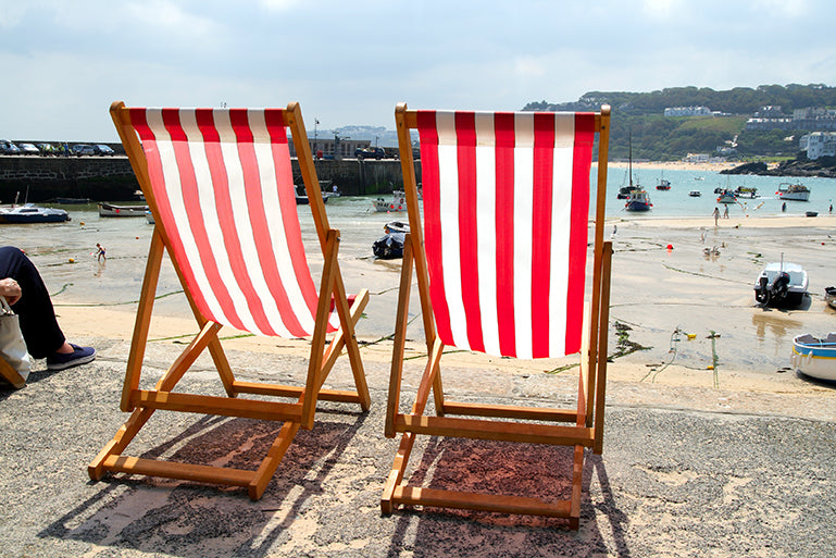 Image of deckchairs overlooking a beach