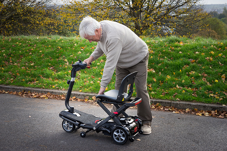 A man folding a Middletons Explorer 4mph boot mobility scooter
