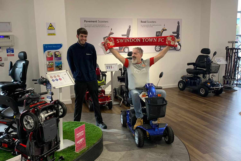 Paul Jacko Jackson receiving a mobility scooter from the swindon store