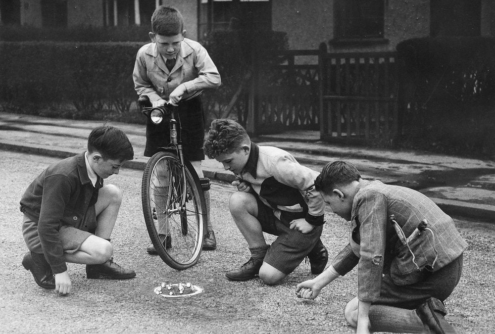 Boys playing marbles in the street