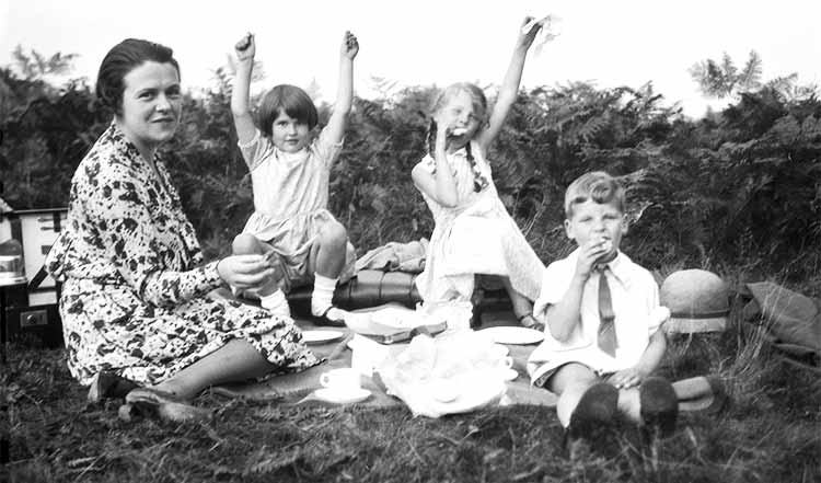 Three children having a picnic with their mother